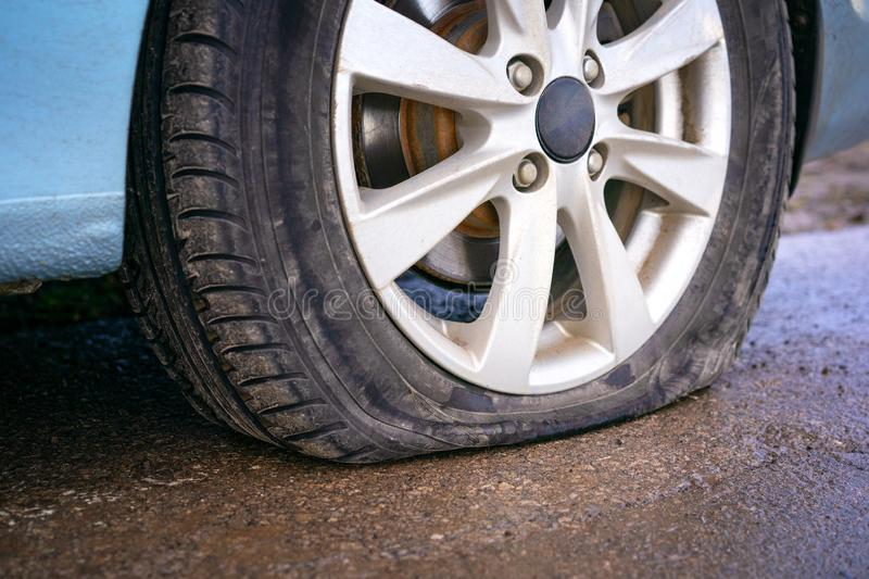 Flat tire of blue car on the road waiting for repair. Car tire leak because of nail pounding royalty free stock photos