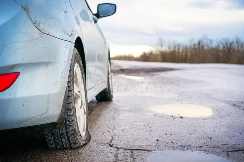 Flat tire of blue car on the road waiting for repair. Car tire leak because of nail pounding royalty free stock images