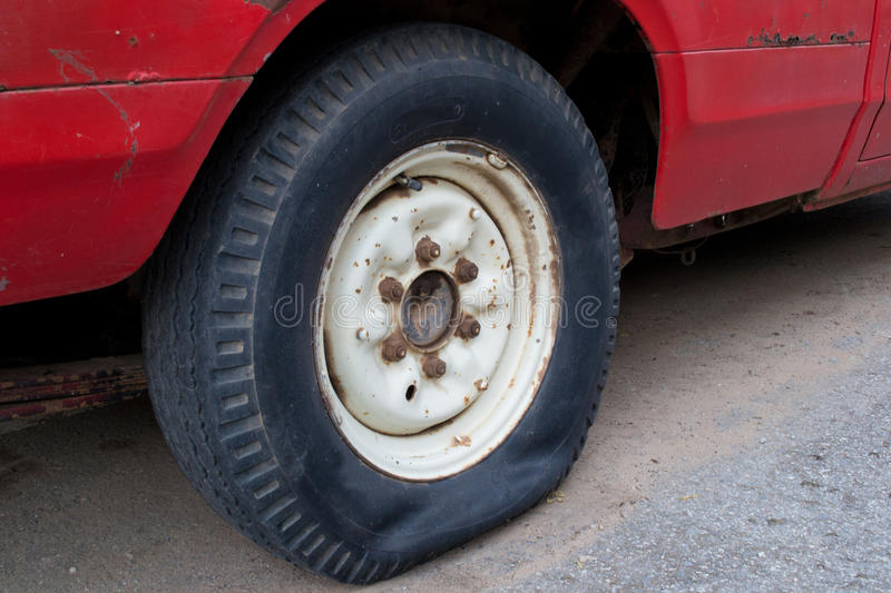 Flat tire. Closeup of flat tire on the road royalty free stock image