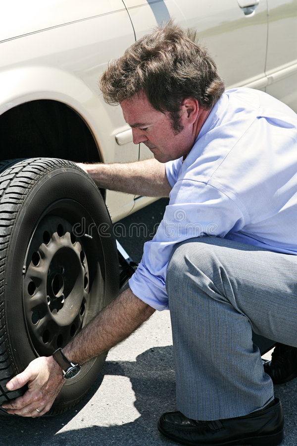Flat Tire - Dirty Job. A businessman changing a flat tire on the road, red faced from the heat stock photo