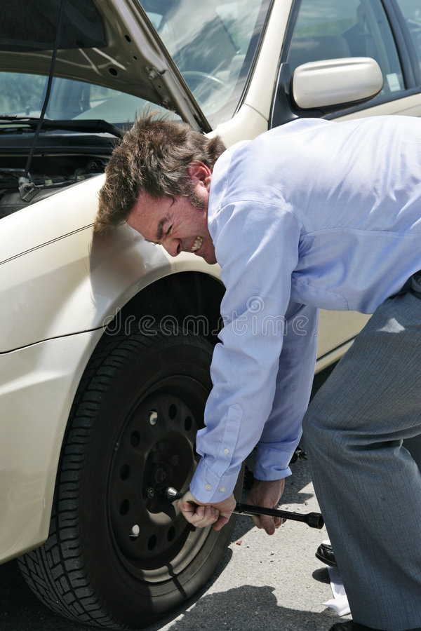 Flat Tire - Effort. A businessman with a flat tire on the road strains to uncrew the lug nuts stock images