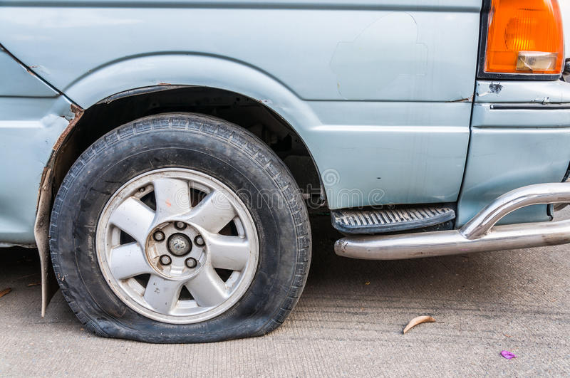 Flat tire. Front of van, flat tire, on concrete road stock photos
