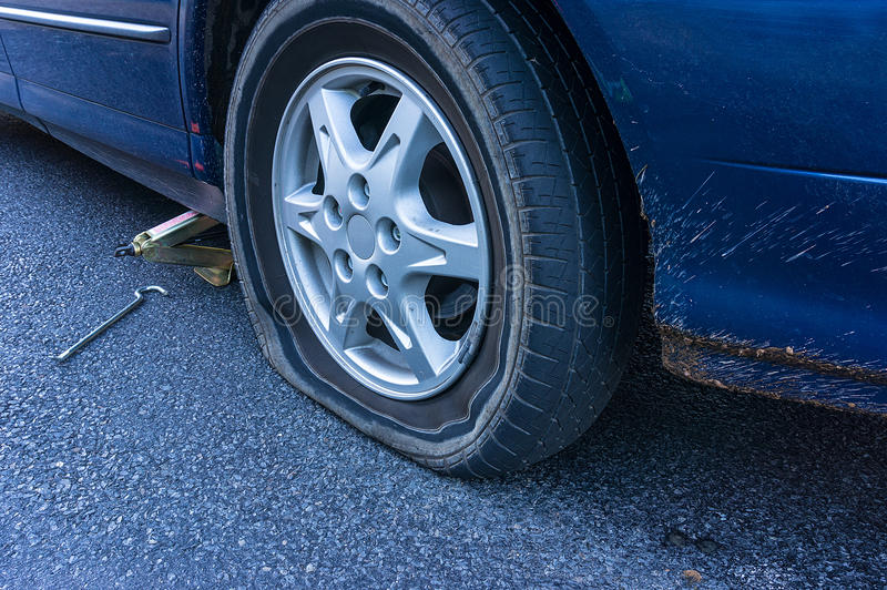 Flat tire on the road. Blue car with flat tire on the road. Flatten tyre royalty free stock photo