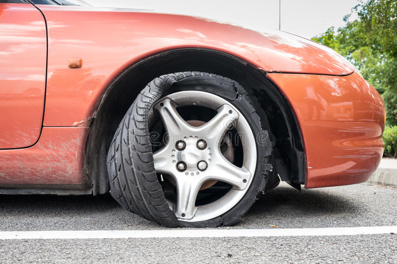 Flat Tire. A vehicle with a flat tire stock image