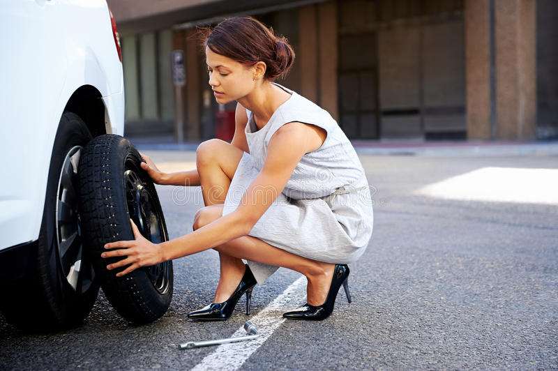 Flat tire woman. Businesswoman in the city with flat tire frustrated royalty free stock photos
