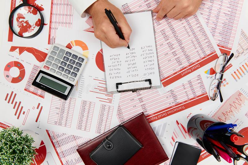 Flat top view of businessman working and calculating finance, reads and writes reports. Business financial accounting concept royalty free stock image