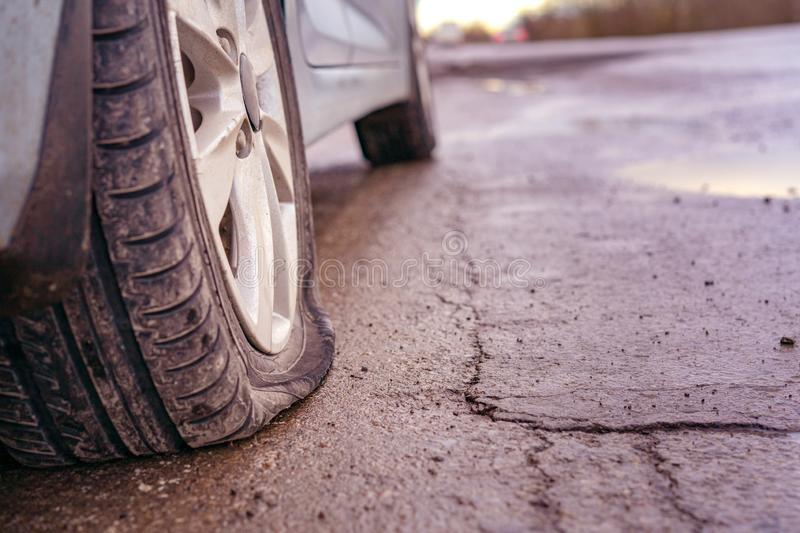 Flat tyre on road. Car tire leak because of nail pounding. Toned royalty free stock photo