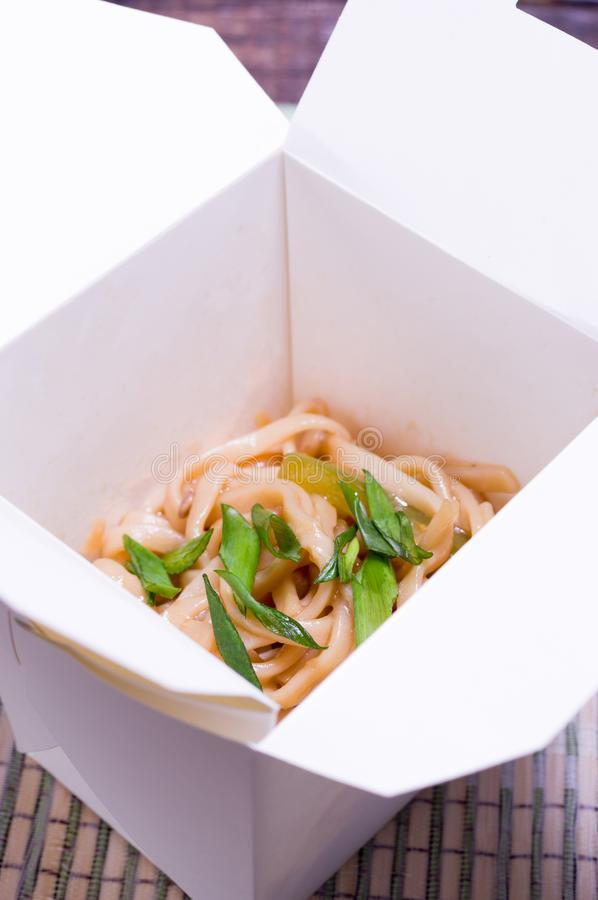 Flat noodles in a cardboard container. Vertical frame royalty free stock photos