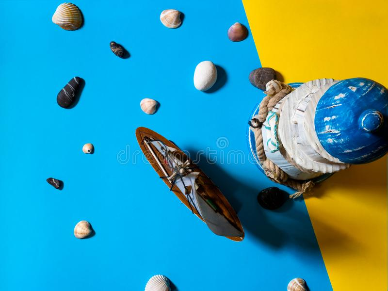 Flat view of toy sailboat and lighthouse on blue and yellow background with sea stones and seashells royalty free stock photography