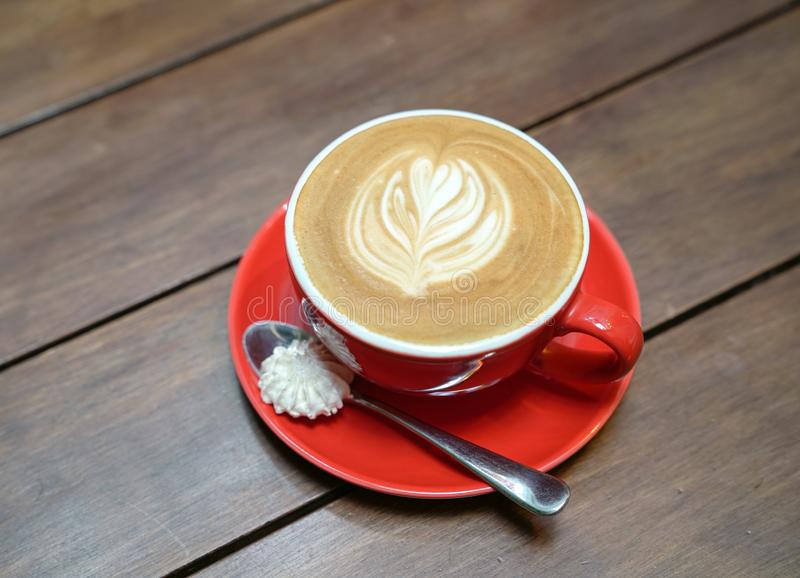 Flat white coffee with heart pattern in a red cup royalty free stock photography