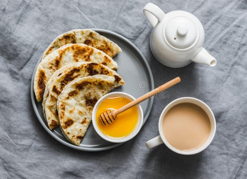 Flatbread indio del paratha con la miel y el t? del masala en el fondo gris, visi?n superior foto de archivo libre de regalías