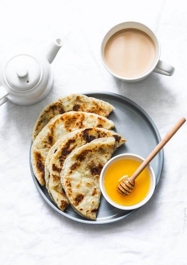 Flatbread indio del paratha con la miel y el té del masala en el fondo ligero, visión superior fotografía de archivo libre de regalías