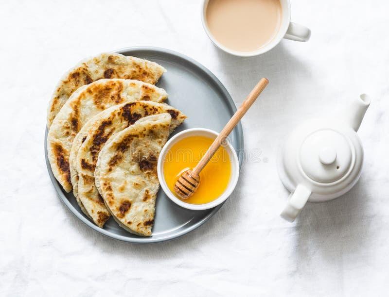 Flatbread indio del paratha con la miel y el té del masala en el fondo ligero, visión superior imagen de archivo libre de regalías