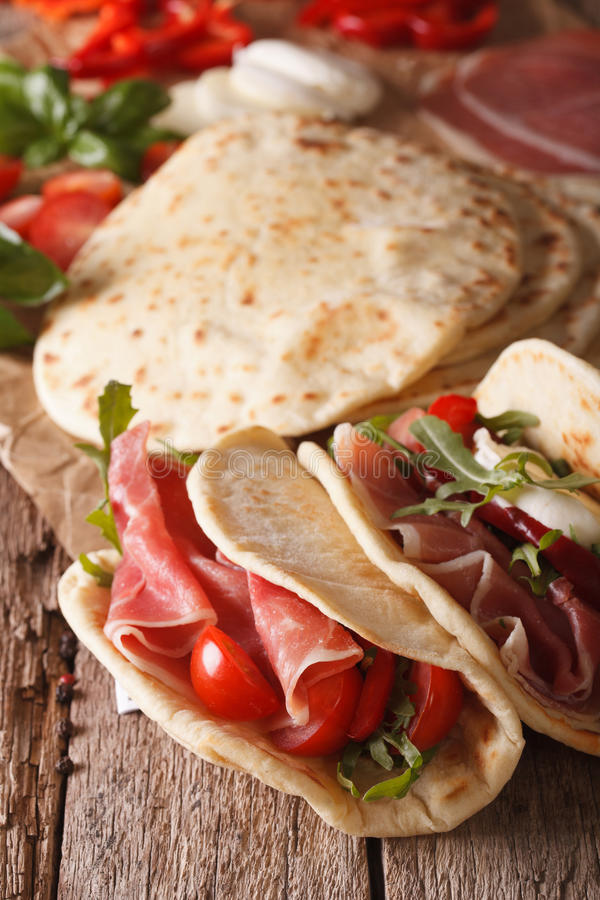 Flatbread italiano di piadina farcito con il prosciutto e le verdure vicino immagini stock