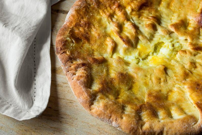 Flatbread rond entier appétissant délicieux avec du fromage remplissant sur le Tableau en bois de serviette blanche Pâtisserie sa photographie stock