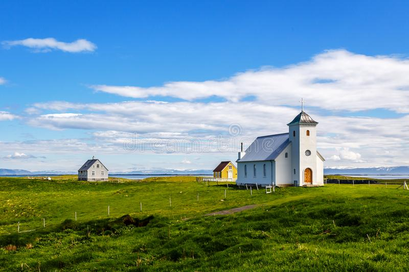 Flateyjarkirkja church and couple of living houses with meadow i. N foreground and sea fjord with blue sky in the background, Flatey, Iceland stock image