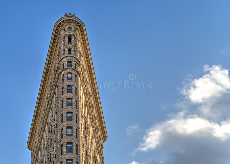 Top of flatiron building over blue sky. Flatiron building - landmark of New York City. Blue sky with clouds on the background royalty free stock photography