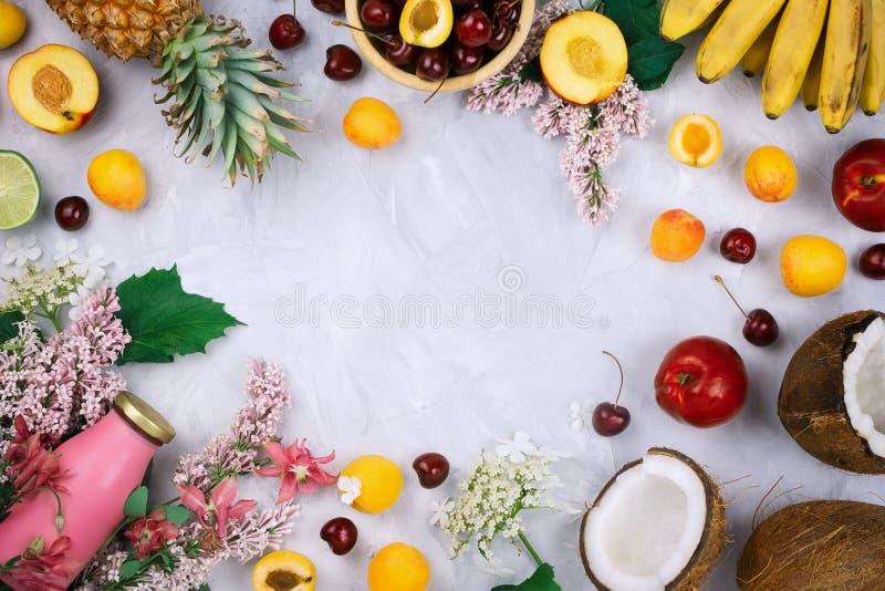 Flatlay框架安排用各种各样的有机果子:香蕉、椰子、菠萝、桃子、新鲜的樱桃、淡紫色花和sm 库存照片