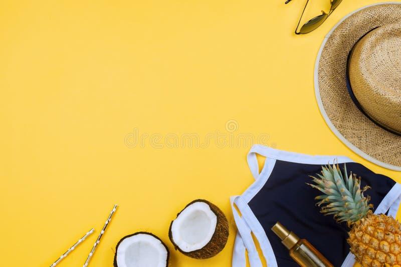 flatlay的暑假与草帽、泳装、椰子一半、机油和玻璃在黄色 免版税库存照片