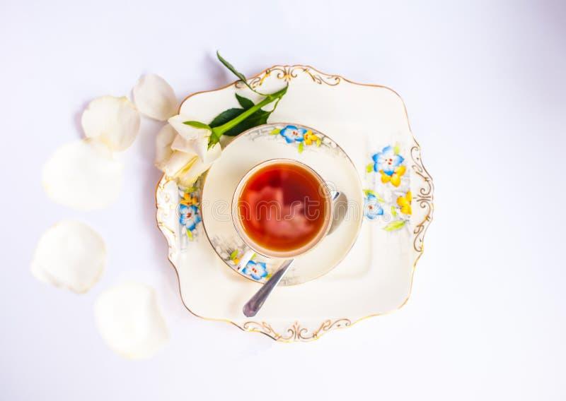 Flatlay με το κομψό τσάι που τίθεται με τη ροδαλή αντανάκλαση λουλουδιών iat στοκ εικόνα