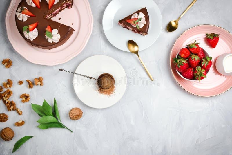 Flatlay με το vegan κέικ σοκολάτας, τις φράουλες, τα ξύλα καρυδιάς, το κακάο και άλλα συστατικά επιδορπίων στοκ εικόνα