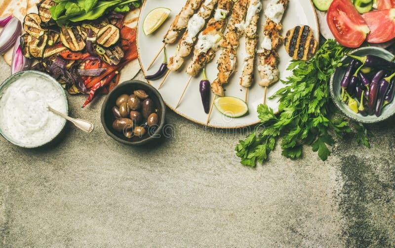 Flatlay των ψημένων στη σχάρα οβελιδίων κοτόπουλου, flatbread, μαϊντανός, λαχανικά, ελιές στοκ εικόνες
