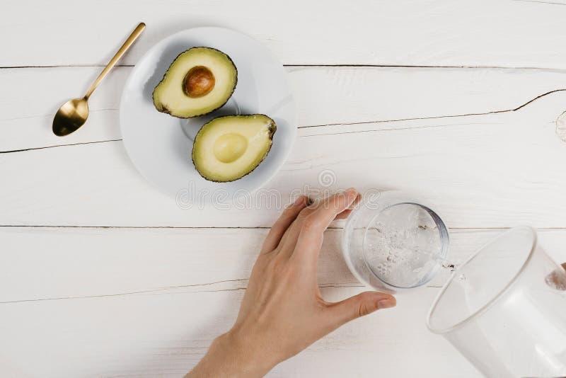 Flatlay с свежими зрелыми половинами авокадоа отрезка и ` s женщины вручают лить чистую воду в стекле на деревянной белой таблице стоковые фотографии rf