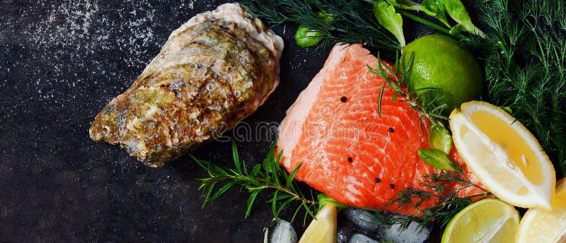 flatlay 新鲜的海鲜的构成在黑暗的背景的 鳟鱼和牡蛎用草本和柠檬 免版税库存图片