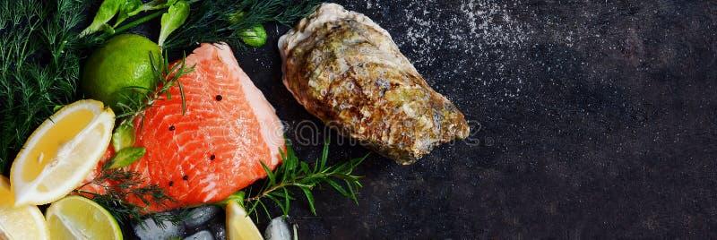 flatlay 新鲜的海鲜的构成在黑暗的背景的 鳟鱼和牡蛎用草本和柠檬 库存照片