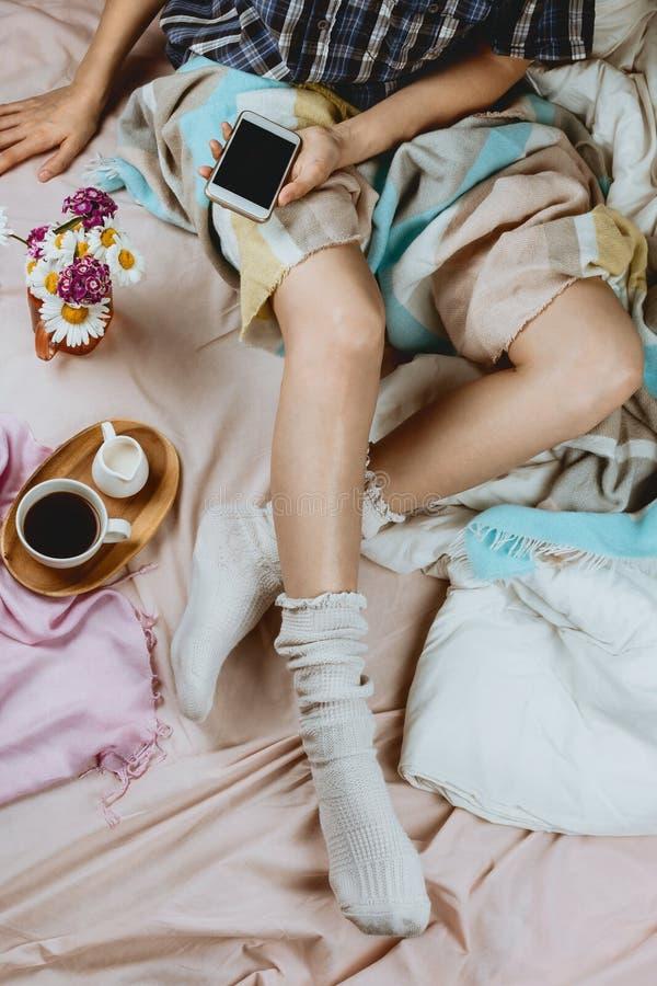 Flatlay accogliente con bianco ha abbronzato la donna in calzini bianchi che si siedono nel suo letto che tiene uno smartphone immagini stock