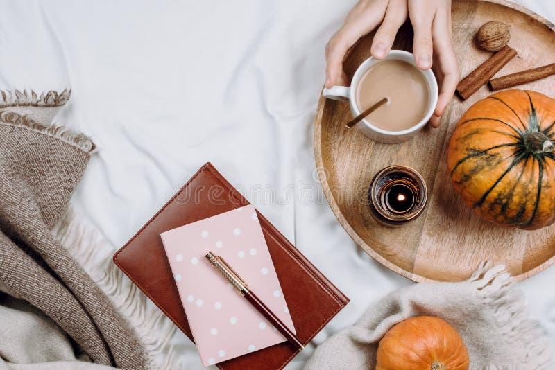 Flatlay acogedor con la bandeja de madera, la taza de café o el cacao, vela, calabazas, cuadernos fotos de archivo libres de regalías