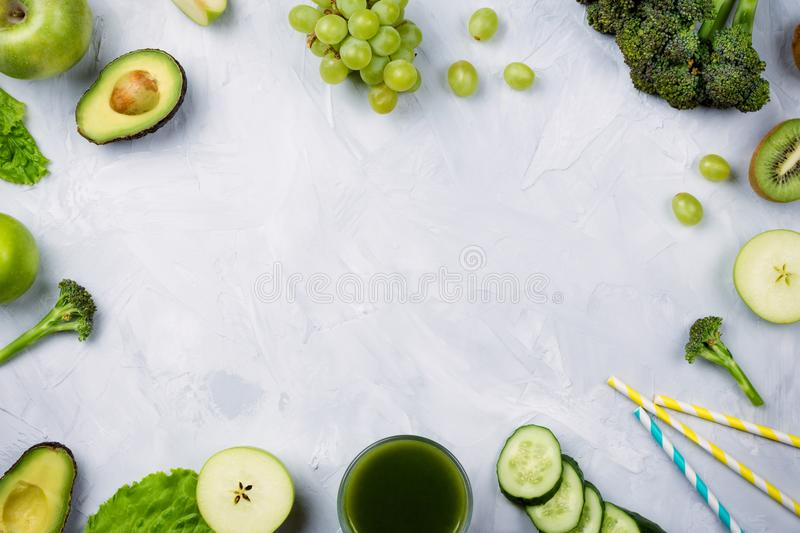 flatlay arrangement with various green fruits and vegetables: lettuce, cucumber, avocado, broccoli, grapes, apples etc royalty free stock image