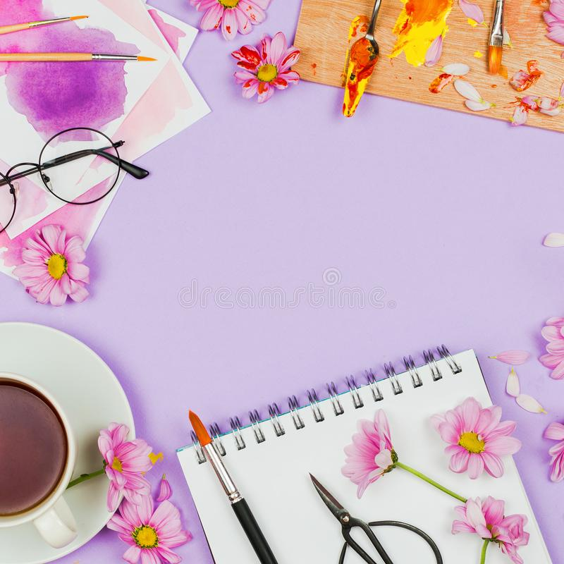 Flatlay with art supplies, artist palette, glasses, flowers, cup of tea and sketchbook. Creativity concept, spring/summer floral composition, flaltlay, violet stock image
