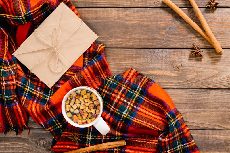 Flatlay autumn composition. Cup of tea, red plaid, vintage envelope, cinnamon stick on wooden background. Flat lay, top view,. Overhead. Cozy home desk, hygge royalty free stock photography