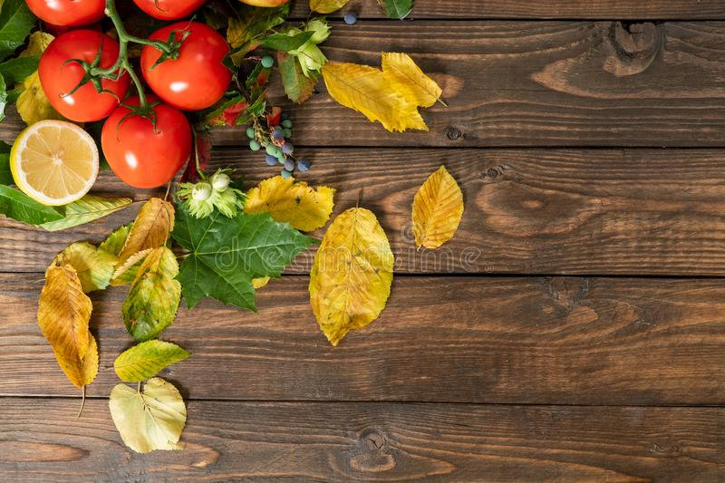 Flatlay autumn composition. Tomato, lemon, autumn fallen leaves on wooden desk. Flat lay, top view, copy space. Agriculture royalty free stock photography
