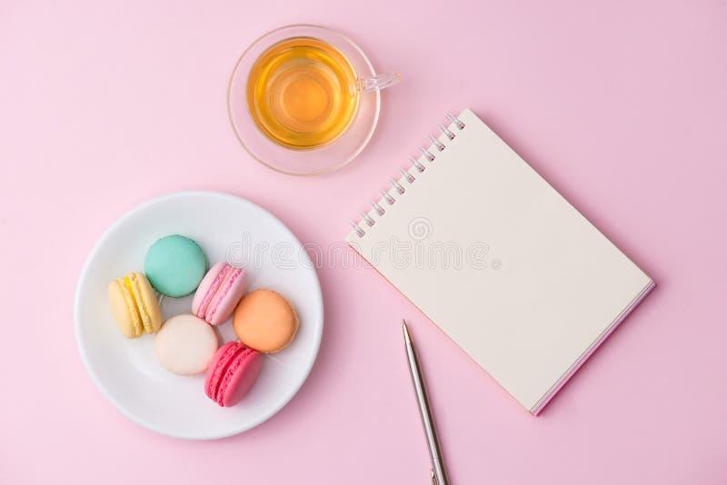 Flatlay av anteckningsboken, kakamacaron och kopp te på rosa färgtabellen fotografering för bildbyråer