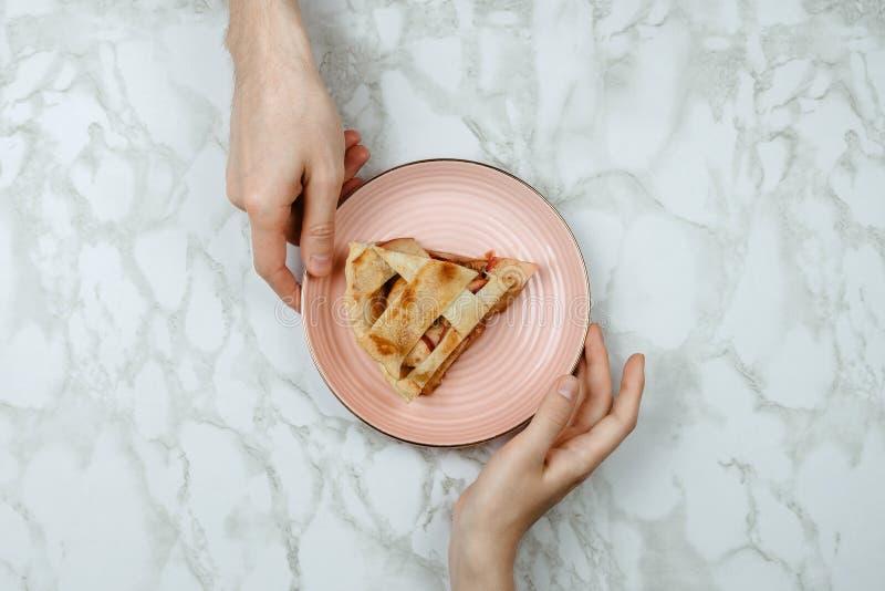 Flatlay av män som passerar stycket av äppelpajen till handen för kvinna` s royaltyfri foto