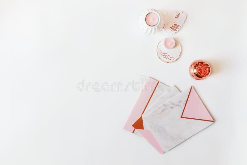 Flatlay av skrivbordtabellen Workspace med modrn som är rosa och marmoranteckningsböcker och garneringar på vit bakgrund arkivfoto