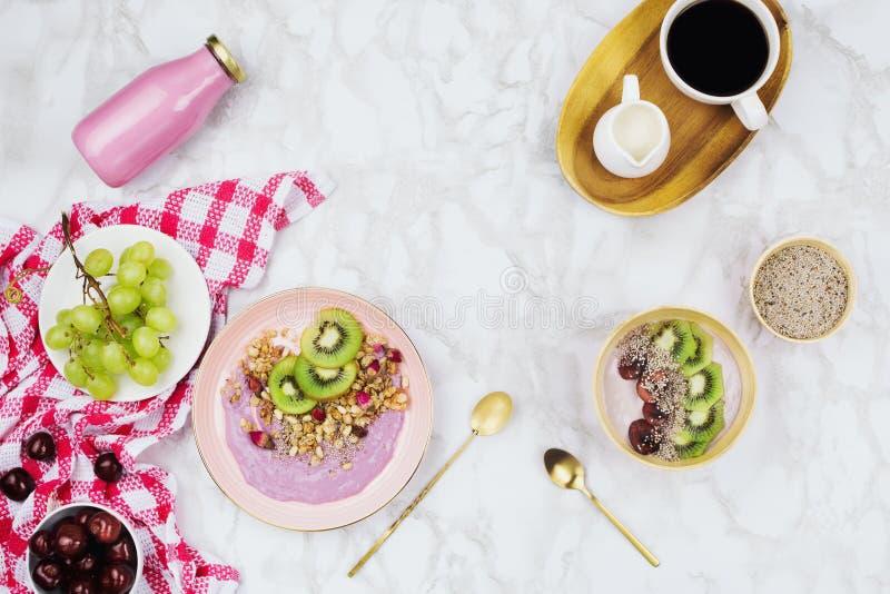 Flatlay av strikt vegetarianfrukosten med växt baserade yoghurtbunkar som överträffas med kiwiskivor, granola, chiafrö, smoothief arkivfoto