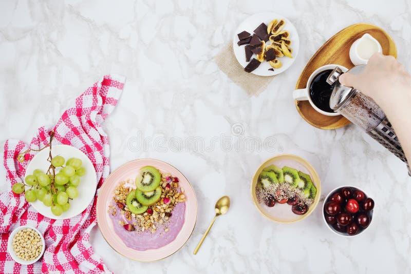Flatlay av strikt vegetarianfrukosten med växt baserade yoghurtbunkar som överträffas med kiwiskivor, granola, chiafrö, smoothief royaltyfri bild