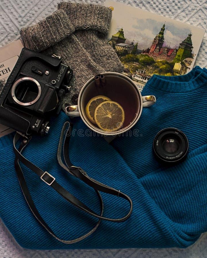 Flatlay av te med citroner, oldschoolkameran, tröjan och böcker fotografering för bildbyråer