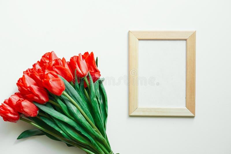 Flatlay av tulpan och fotoramen på vit bakgrund kopiera avst?nd T?m utrymme royaltyfria bilder