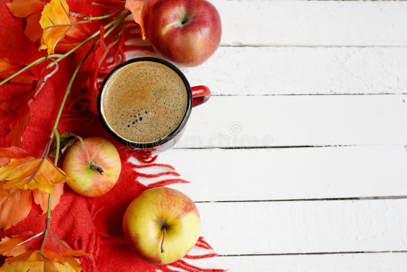 Flatlay bakgrund för höst med koppen kaffe, gula sidor och och röda äpplen på den vita trätabellen, kopieringsutrymme arkivfoton