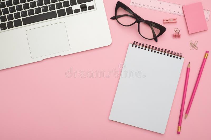 Flatlay bonito com portátil, vidros e artigos de papelaria no de cor-de-rosa fotos de stock royalty free