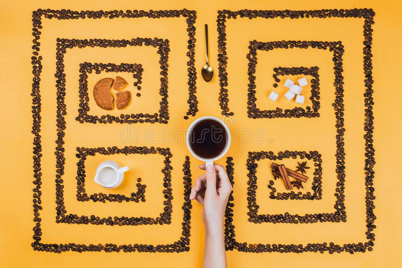 Flatlay of coffee cup in the middle of pattern or labyrinth made of coffee beans royalty free stock photos