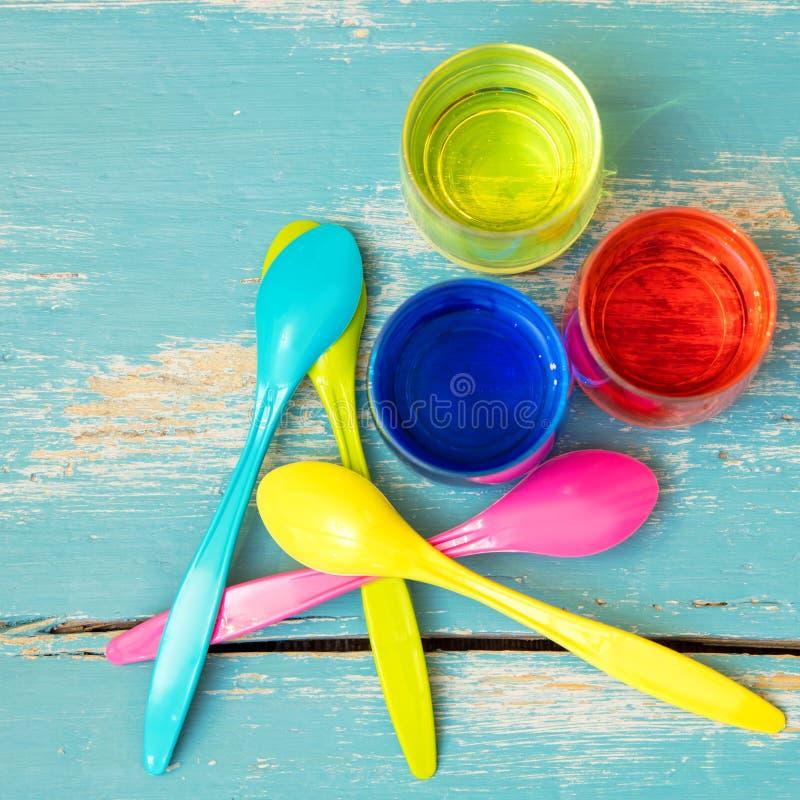 Flatlay, colheres coloridas do ovo e tinturas do ovo na tabela de madeira azul imagem de stock royalty free