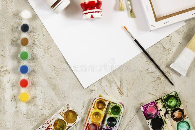 Flatlay com pinturas brilhantes em uns recipientes redondos pequenos e em umas muitas paletas, escova e a folha de papel branca n foto de stock royalty free