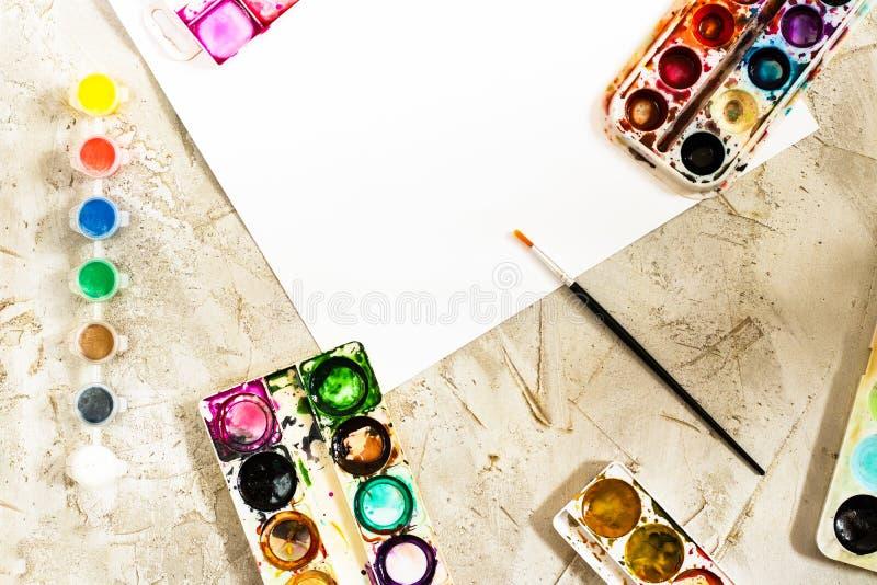 Flatlay com pinturas brilhantes em uns recipientes redondos pequenos e em umas muitas paletas, escova e a folha de papel branca n fotografia de stock royalty free