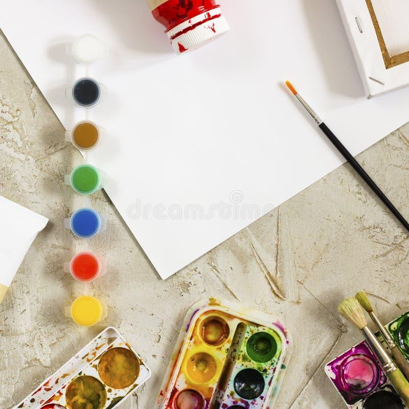 Flatlay com pinturas brilhantes em uns recipientes redondos pequenos e em umas muitas paletas, escova e a folha de papel branca n imagens de stock royalty free