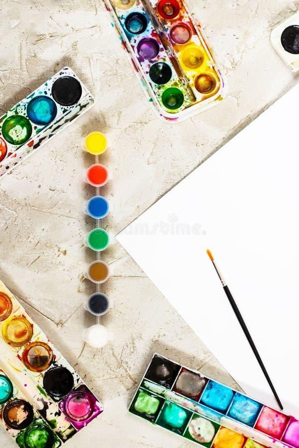 Flatlay com pinturas brilhantes em uns recipientes redondos pequenos e em umas muitas paletas, escova e a folha de papel branca n imagem de stock royalty free